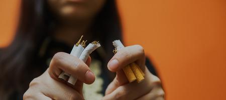 Crop woman breaking cigarette and quitting smoking. Woman smoking