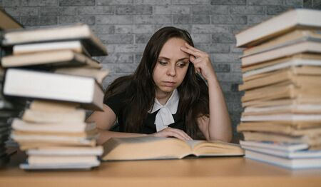 Woman student boring reading book at library with a lot of books in university. Student disheartened reading book for examination. Archivio Fotografico - 124717424