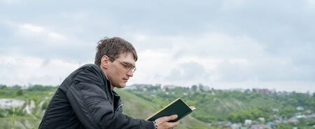 Man reading book in green hilly field. Side view of young handsome man in glasses and warm jacket reading book in open space on background of green hills Imagens