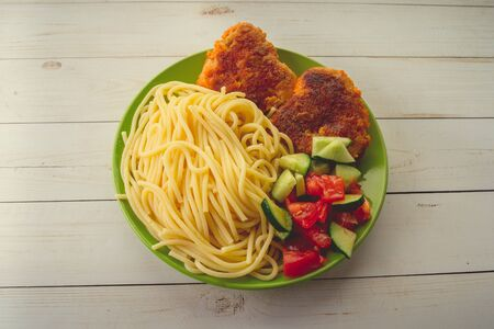 traditional dish consisting of spaghetti with chicken cutlets and vegetable salad. 免版税图像