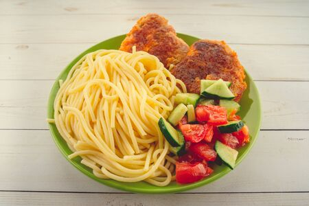 traditional dish consisting of spaghetti with chicken cutlets and vegetable salad.