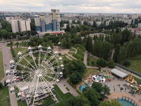 Ferris wheel is in the Park. The Park is a landscaped area created for recreation. It is a place of pleasant pastime for people.