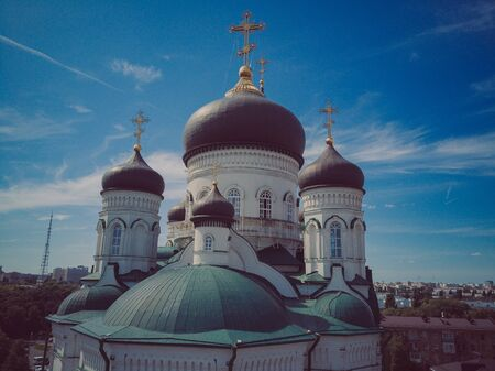 Golden domes with a crosses on the Christian Orthodox Church shine on a sunny day against blue sky.