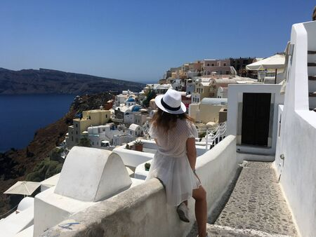 A young woman in a white dress and a white hat is looking at the sea.