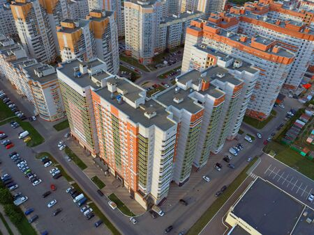 Drone view of new building complex in city center with houses