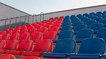 Red and blue seats in a large street stadium. Imagens