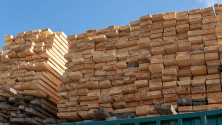 Wooden boards, lumber, industrial wood, timber. Pine wood timber stack of natural rough wooden boards on building site.