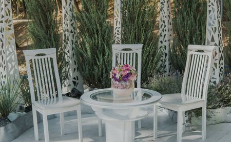 White chairs and table with bouquet of flowers outdoor.