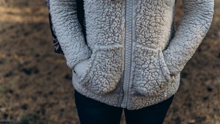 The woman put her hands in her pockets to keep warm on a cold autumn day.