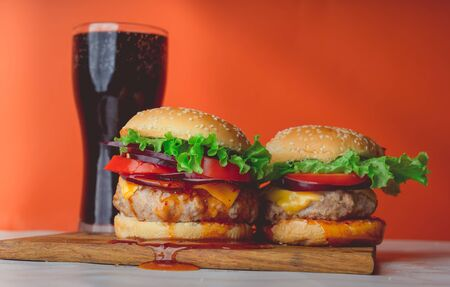 A two huge juicy hamburger is on a chopping board and large glass with coke Reklamní fotografie