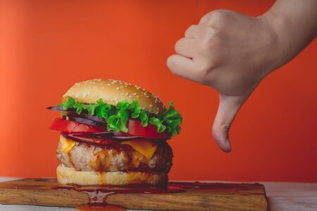 A huge juicy hamburger is on a chopping board. Womans hand shows a sign of dislike.