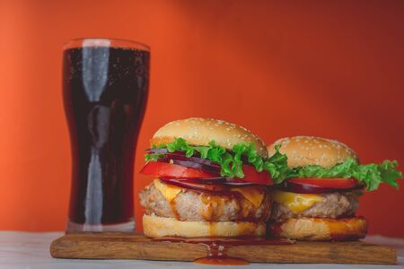 A two huge juicy hamburger is on a chopping board and large glass with coke 写真素材
