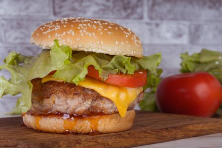 A huge juicy hamburger is on a chopping board with vegetables