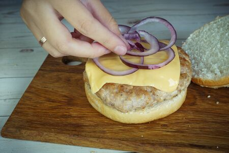 Women's hands are preparing a big hamburger. Cheeseburger of the homemade