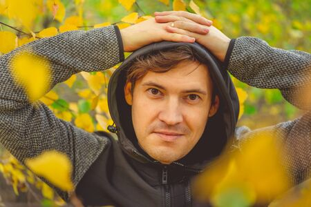 Portrait of a young handsome man in casual clothes against the yellowed trees in the autumn forest. Banque d'images