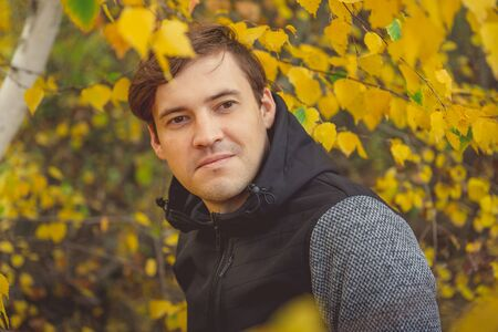 Portrait of a young handsome man in casual clothes against the yellowed trees in the autumn forest.