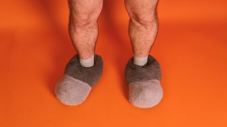 Mens feet in socks and warm big slippers on an orange background