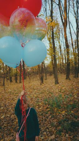 A little girl are holding balloons on walk in autumn forest