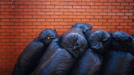 A big pile of garbage bags on the asphalt near a brick building. Stok Fotoğraf