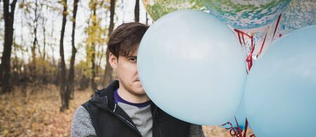 A young handsome man is holding the colorful balloons on walk in autumn forest