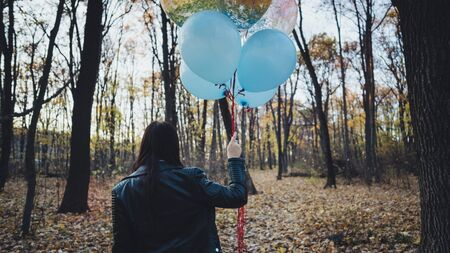 A young beautiful woman in casual clothes is holding the colorful balloons on walk in autumn forest 版權商用圖片