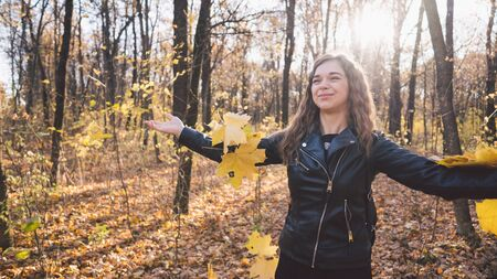 A beautiful young woman in casual clothes tossed the yellow leaves up in the autumn forest. The foliage fly in different directions and the charming woman laughs cheerfully.