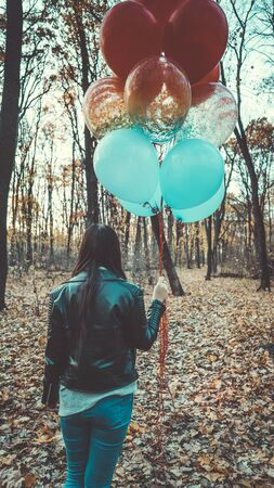 A young beautiful woman in casual clothes is holding the colorful balloons on walk in autumn forest Imagens