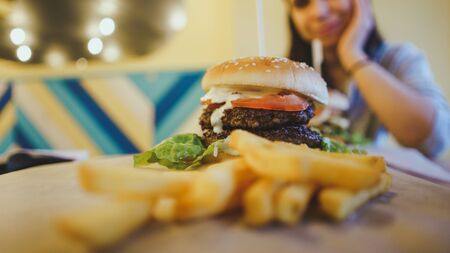 A big juicy burger with two cutlets, vegetables, sauce and french fries on the table in a cafe Imagens