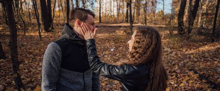 A woman's hand hits a man's face in the autumn forest.
