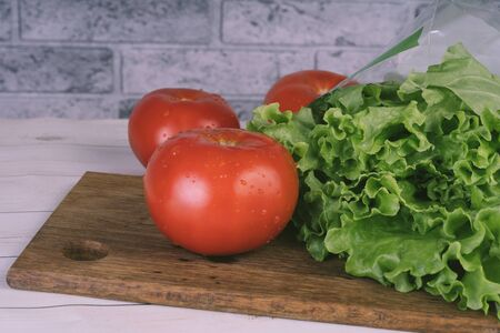 Red tomatoes with water droplets and green lettuce are on a wooden board Imagens