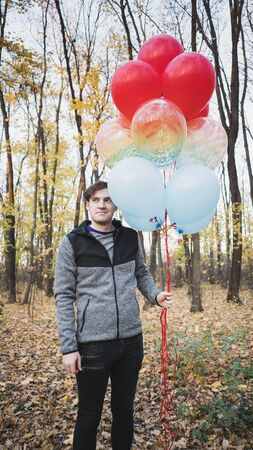 A young handsome man is holding the colorful balloons on walk in autumn forest.