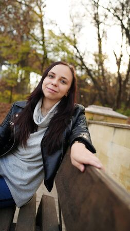 A young beautiful woman in casual clothes is sitting on a bench in autumn park Imagens