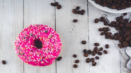 A delicious donut is in a small plate with coffee beans. The coffee beans are scattered near a white plate for decoration Close up. Stok Fotoğraf