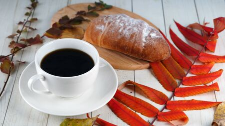 A steaming cup of coffee with coffee beans and a croissant on vintage wooden table.