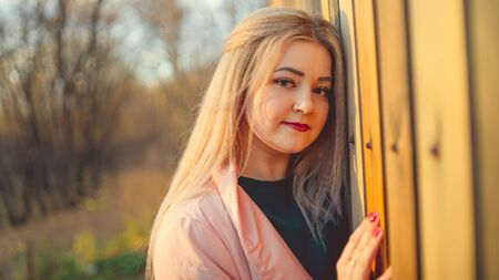 A portrait of a beautiful girl, posing near a wooden fence at sunset in springtime