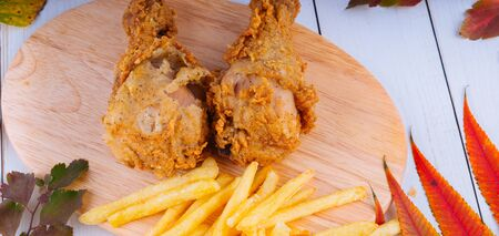 Two breaded chicken legs with french fries are on a wooden board.