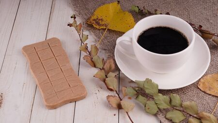 A hot cup of coffee with a bar of chocolate on the table in a cafe. Imagens