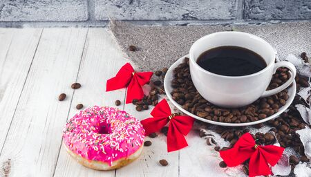 A hot cup of coffee with a doughnut and the coffee beans on the table.