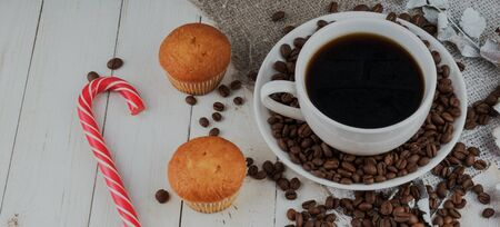 Close up still life, cup of coffee with muffins. Freshly baked delicious muffins and cup of coffee on wooden table.