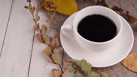 Cup of coffee with coffee beans on vintage wooden table. Homemade coffee or americano.