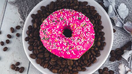 A delicious donut near a small white plate with coffee beans. The coffee beans are scattered on the table for decoration. Close up.