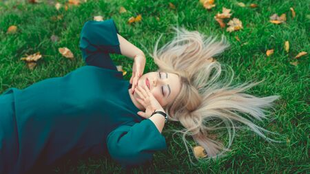 A portrait of a beautiful girl, lying on the grass. A charming woman lies on the green grass with yellow leaves Imagens