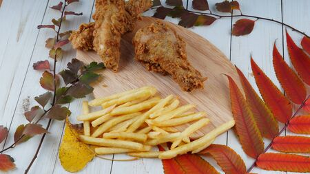 Two breaded chicken wings, one chicken leg and a bunch of golden french fries are on a wooden board with decoration of autumn leaves