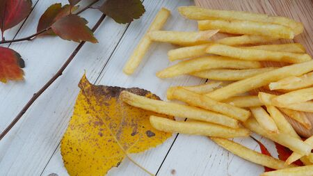 The appetizing french fries are on a wooden board with decoration of autumn leaves