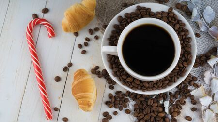 A hot cup of coffee with the coffee beans, small croissants and a candy on the table.