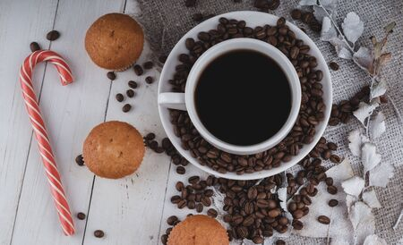 A hot cup of coffee with the coffee beans, small cupcakes and a candy on the table. Imagens