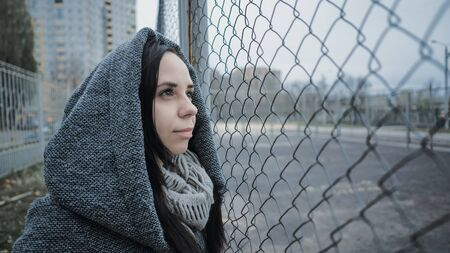 A young beautiful woman in the gray coat poses near a lattice fence in a late autumn