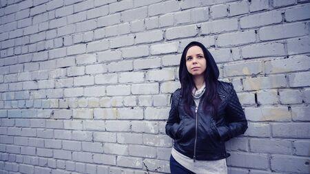 Posing near white brick wall. Sad girl looking to the side Stock fotó
