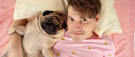Handsome man lying with dog at bed. Young man in a bed under a rug with his dog in an embrace