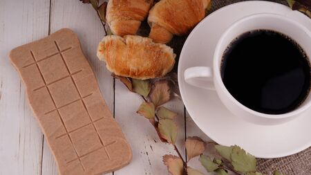 A hot cup of coffee with a bar of chocolate on the table in a cafe. Фото со стока